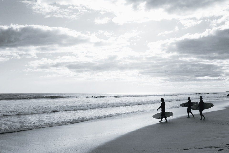 3 guys walking for a surf